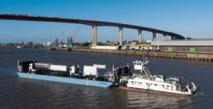 Barge et bateaux pousseurs transportant des camions devant le pont de Saint-Nazaire