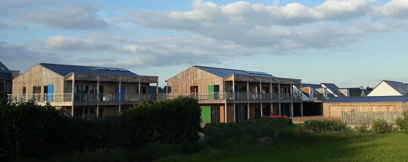 Habitat participatif, Guérande (département 44) : bâtiment bois, large baies vitrées donnant sur des coursives, volets bleus et verts