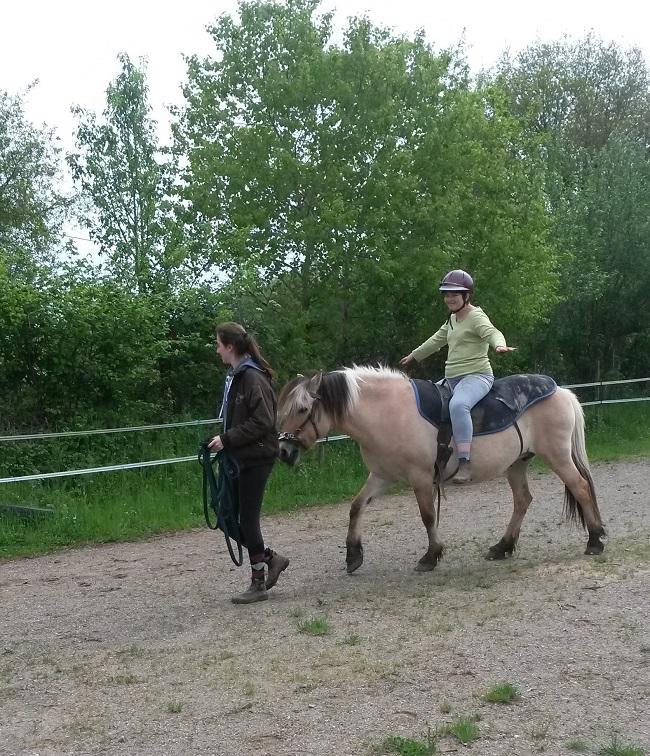 Jeune handicapée en situation de handicap mental faisant du cheval sans les mains, la longe du cheval est tenue par une encadrante
