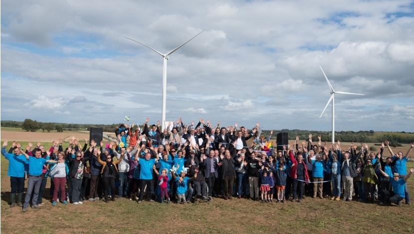 groupe d'habitants investis dans une des coopératives citoyennes d'énergie, posant devant leur éolienne en arrière plan