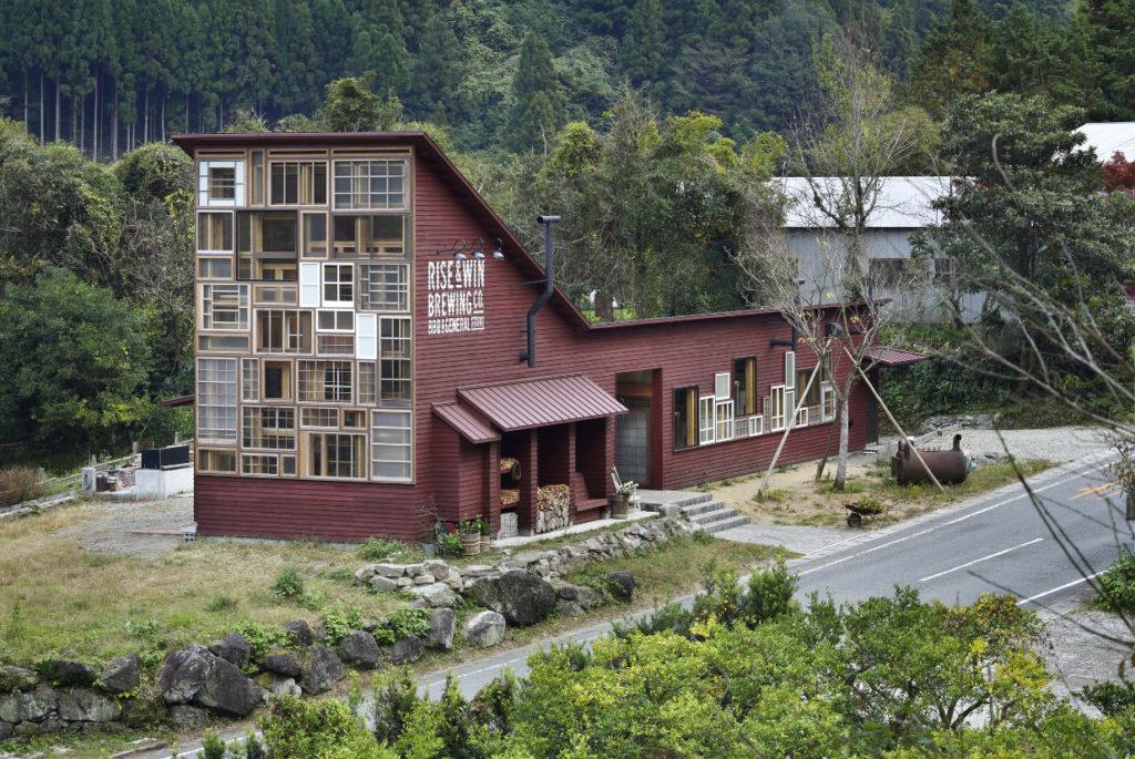Exemple surprenant d'économie circulaire : bâtiment en bois avec une grande façade entièrement vitrée composée de nombreuses fenêtres de récupération de toutes formes.