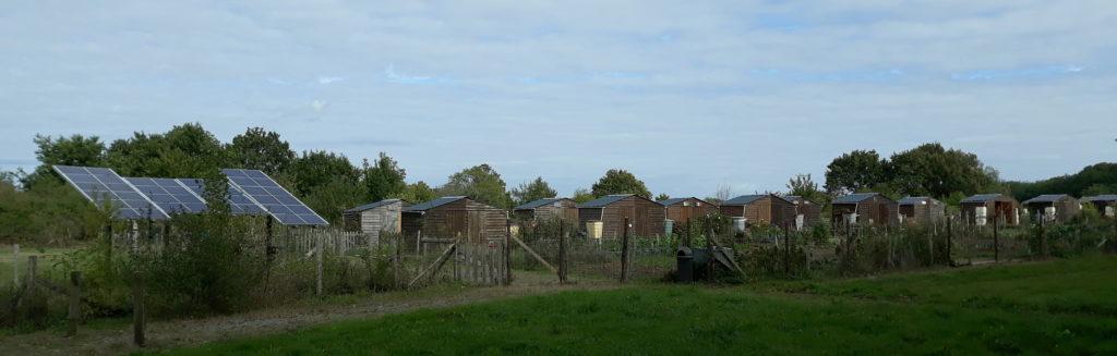 Vue des jardins partagés de Donges : panneaux solaires photovoltaïques au sol, série de cabanes en bois avec récupérateur d'eau et parcelles individuelles, le tout enclos d'une clôture