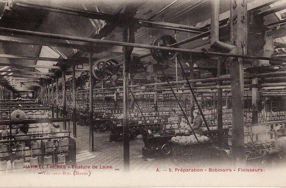 La filière laine au  XIXe siècle : carte postale en noir et blanc de la filature Harmel Frère, énorme hangar, machines anciennes à perte de vue, courroies, femmes et bobines de laine au premier plan
