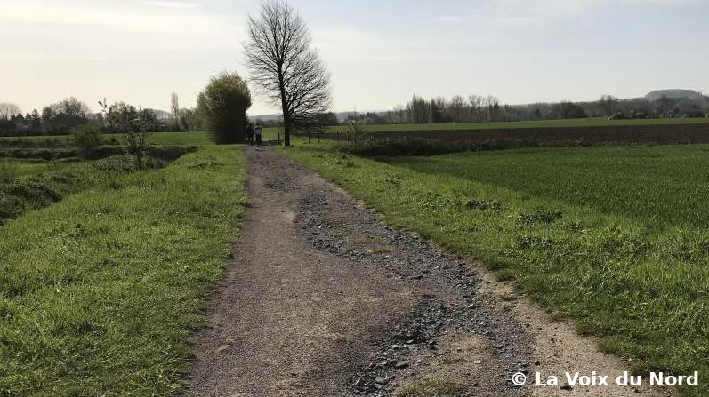 Piste cyclable à travers la campagne, champs de chaque côté, haies à l'arrière-plan. Cette voie verte est abîmée : présence d'ornières creusées par la pluie, révélant les gros cailloux présents sous le stabilisé.