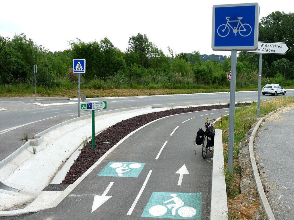 Piste cyclable en campagne, sécurisée, séparée de la route par un parapet en béton. Piste neuve, en bon état, peinture propre au sol, panneaux routiers spécifiques vélo