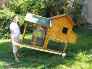 """Poulailler mobile en bois d'environ 2 m², sur roues, transportable comme une brouette grâce à deux poignées. Le poulailler se compose d'une partie """"maison"""" et d'une partie """"extérieure"""" en grillage."""