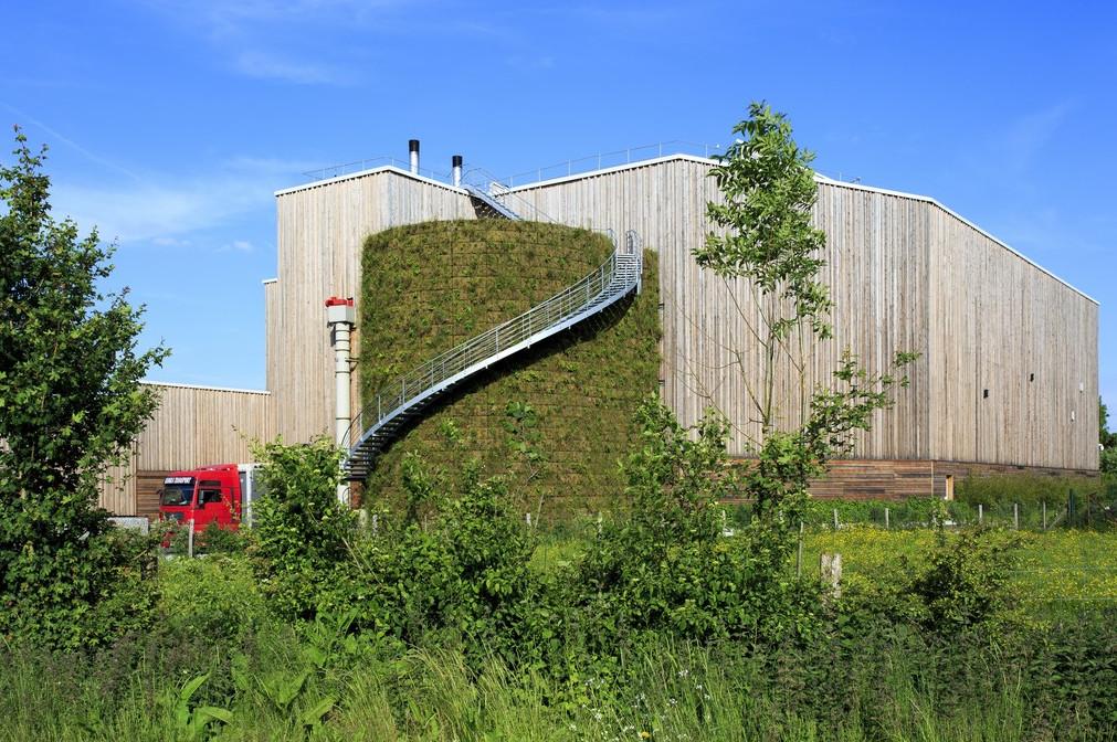 Vue d'une citerne industrielle entièrement recouverte de végétaux (mur industriel végétalisé), devant une usine avec bardage en bois