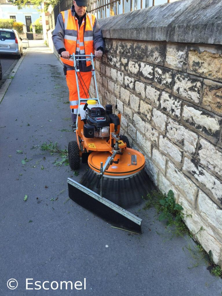 Agent d'entretien d'espaces verts dans une rue poussant une balayeuse mécanique, le long d'un mur, pour enlever les herbes sauvages poussant au pied de ce mur